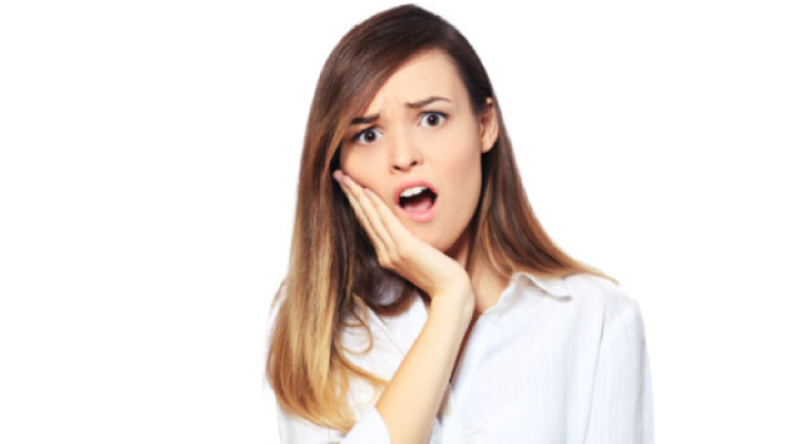 young woman holds her jaw in pain with a dental emergency