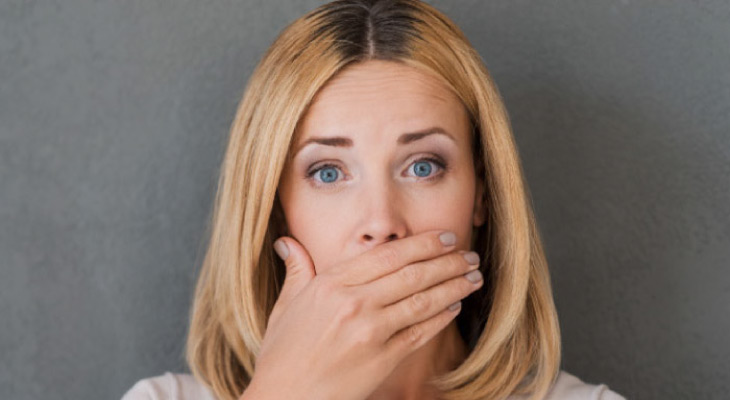 woman covering her mouth to hide periodontal disease