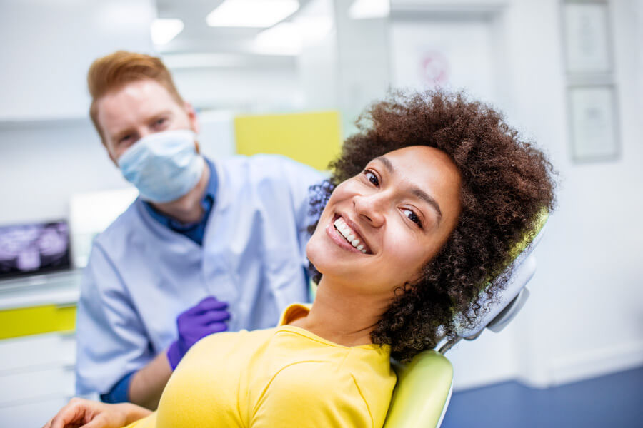 Curly haired woman in a yellow shirt smiles while sitting in the dental chair at the dentist in Tampa, FL