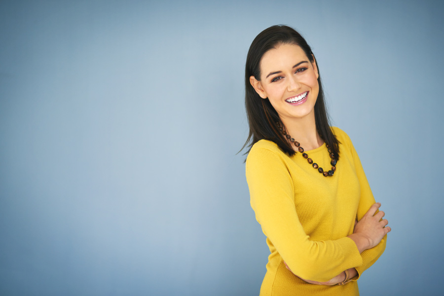 Brunette woman smiles after a smile makeover with veneers in Temple Terrace, FL, in a yellow blouse