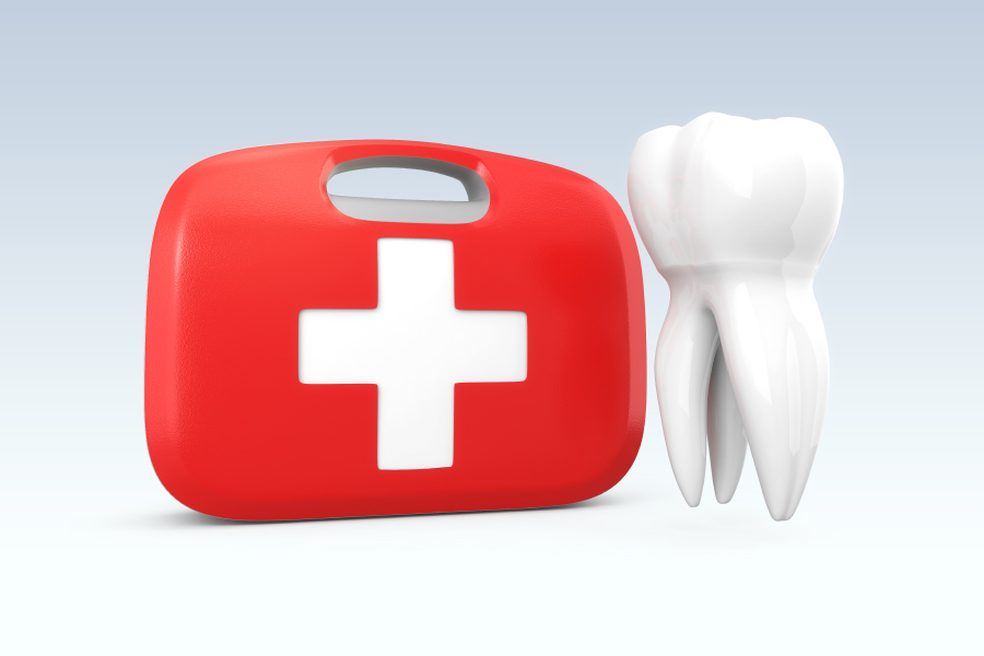 A red first aid kit next to a white tooth to indicate a dental emergency