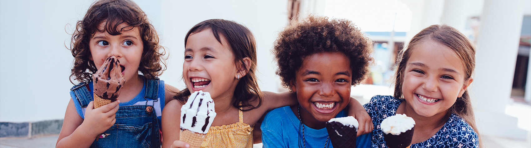 Children laughing and smiling while eating ice cream