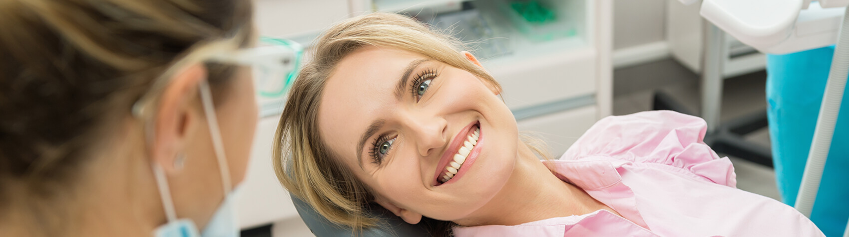 Patient smiling up at dentist during exam